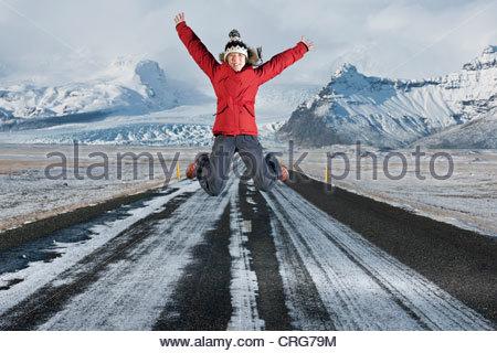 Donna salta su strada nel paesaggio innevato Foto Stock
