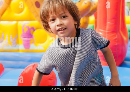 Ragazzo giocando in castello gonfiabile, ritratto Foto Stock