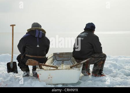 Due saldatori Inuit seduti a bordo di ghiaccio sulla loro barca a remi e si affacciano sul mare aperto, Groenlandia, Foto Stock