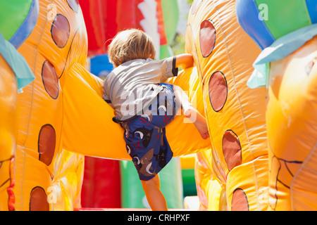 Ragazzo giocando in castello gonfiabile, vista posteriore Foto Stock