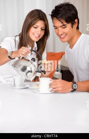 Coppia giovane avente la colazione a casa cercando felice Foto Stock