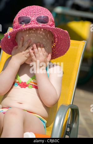 Bambina in un bikini con un cappello per il sole seduti in un seggiolino per bambino tenendo le mani davanti ai Foto Stock