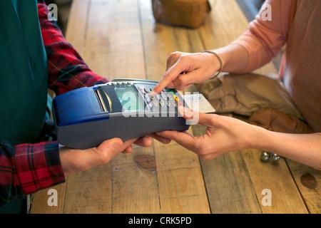 Donna fare shopping con la carta di credito in negozio