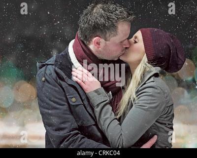 Giovane kissing nella neve durante la notte Foto Stock