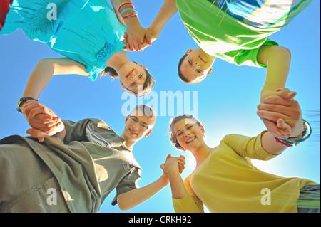 Quattro bambini tenendo le mani Foto Stock