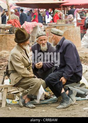 Anziani cinese uigura uomini in abiti tradizionali al mercato locale nella piccola cittadina di Upal, Cina. Foto Stock
