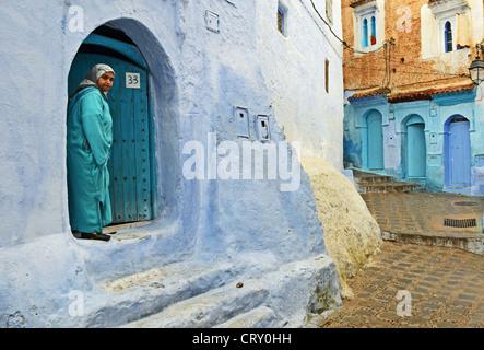 Donna in porta, Chefchaouen, Marocco Foto Stock