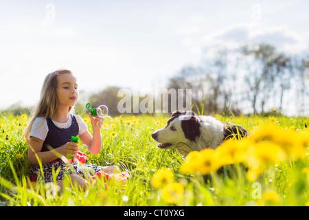 Ragazza a soffiare bolle con il cane nel campo Foto Stock