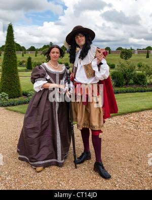 L uomo e la donna nel periodo abito in privato giardino anteriore di Christopher Wren's estensione di Hampton Court Palace