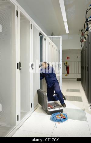 Tecnico operante in sala server Foto Stock