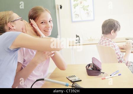 Gli studenti whispering nel laboratorio di tecnologia Foto Stock