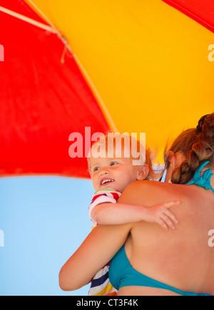 Azienda madre baby cercando su copia spazio sulla spiaggia sotto ombrellone Foto Stock