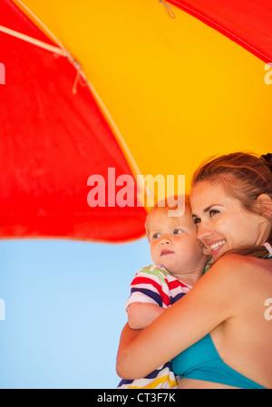 La madre e il bambino cerca su copia spazio sulla spiaggia sotto ombrellone Foto Stock