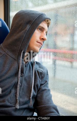 Ritratto di un giovane uomo, perso in pensieri, durante i trasferimenti in treno in un giorno di pioggia Foto Stock