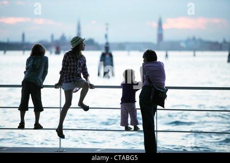 La famiglia presso il molo del Lido di Venezia, vista verso Venezia, Veneto, Italia Foto Stock