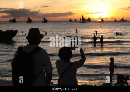 Due turisti fare foto al tramonto, Boracay, Panay Island, Visayas, Filippine Foto Stock