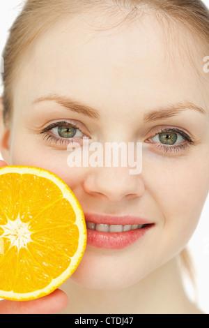 In prossimità di una donna collocando un arancio sulle labbra Foto Stock