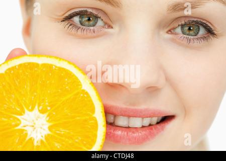 In prossimità di una donna collocando un arancio vicino a sua labbra Foto Stock