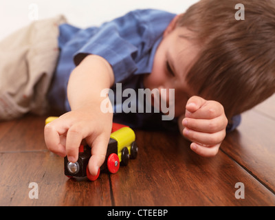 Ragazzo giocando con un trenino sdraiato sul pavimento di legno duro Foto Stock