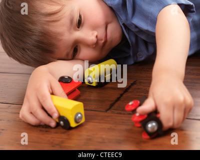 Due anni di vecchio ragazzo giocando con un coloratissimo giocattolo di legno treno su pavimento in legno duro Foto Stock