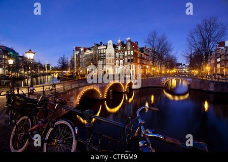 Amsterdam, crepuscolo, attraversamento di canali chiamati Keizersgracht en Leidsegracht. Ponti illuminati, biciclette. UNESCO - Sito Patrimonio dell'umanità.