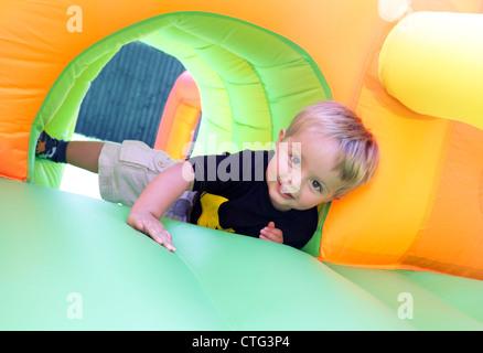 Bambino sul castello gonfiabile Foto Stock