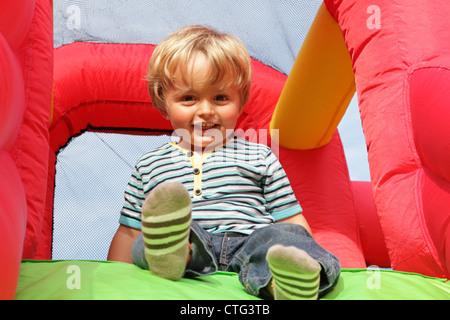 Bambino su gommoni bouncy castello Foto Stock