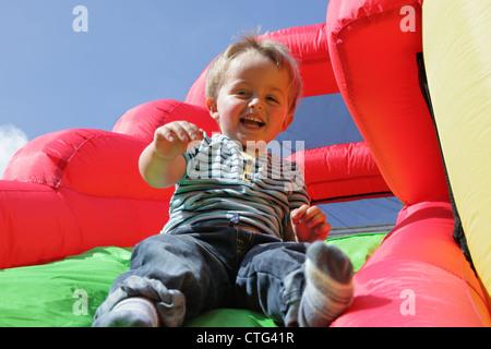 Bambino su gommoni bouncy castello slitta Foto Stock