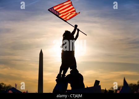 Due immigrati sulla sommità della piramide umana sventola una bandiera americana a Iwo Jima fashion a marzo degli Foto Stock