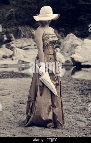 Una giovane donna in un periodo romantico abito in piedi sulla riva di un lago