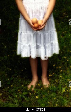 Ragazza è a piedi nudi sull'erba e contiene tre uova crude nelle sue mani Foto Stock