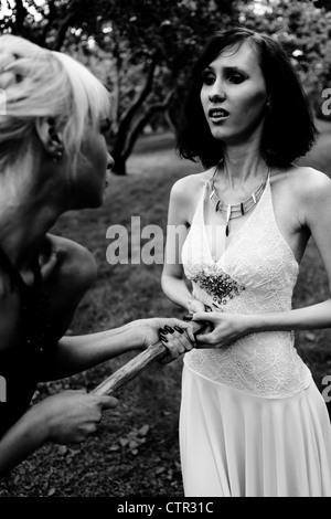 Lotta contro il vampiro: strega e giovane guerriero donna con aspen polo (gioco) al forest Foto Stock