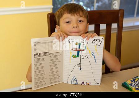 7 anno vecchio ragazzo Mexican-American mostra off disegno realizzato in notebook mentre a casa durante le vacanze Foto Stock