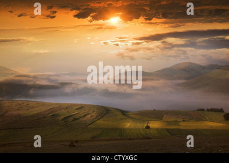 Tramonto nel cielo drammatico su campi Foto Stock