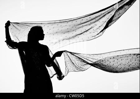 Ragazza indiana con star veli modellata dal vento. Silhouette. Monocromatico Foto Stock