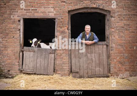 Agricoltore in piedi alla porta del granaio Foto Stock