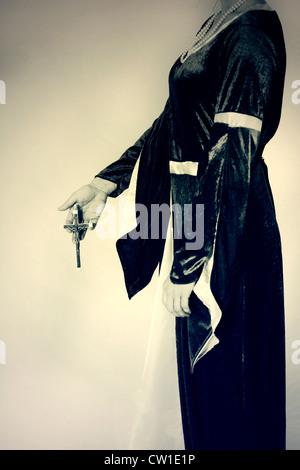 Una donna in abito vittoriano tenendo un crocifisso nelle sue mani Foto Stock