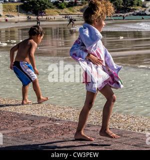 I bambini piccoli sono quasi soffiato con i piedi vicino alla spiaggia a ventoso Gordon's Bay, Western Cape, Sud Foto Stock