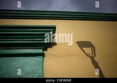 L'ombra di un lampione è colato su di una parete di colore giallo in una casa coloniale di Oaxaca, Messico, 10 luglio Foto Stock