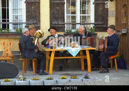 I clienti abituali' tabella di una band di musicisti più anziani di fronte una taverna Foto Stock