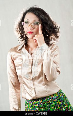 Ritratto di una parentesi dai capelli ragazza asiatica con gli occhiali, la foto è stata scattata in un monolocale.