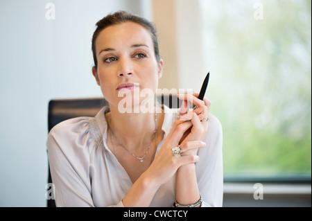Close-up di una imprenditrice di pensare in un ufficio Foto Stock