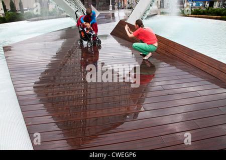 Giovane donna di scattare le foto dei bambini al di sotto dei libertà fontana, Fontanna Wolnosci, in Piazza della Foto Stock