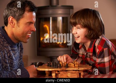 Padre e Figlio giocando a scacchi da caminetto Foto Stock
