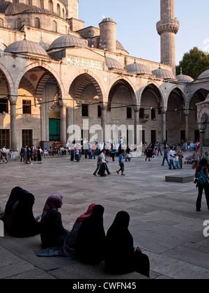 Turisti e fedeli nel cortile della Moschea Blu, Sultanahmet, Istanbul, Turchia Foto Stock