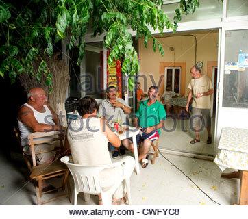Il greco uomini di mangiare la cena in un villaggio di coffee shop gli abitanti di un villaggio di Grecia persone Foto Stock