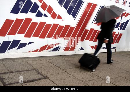 Uomo con una valigia passando una grande Unione bandiera nel centro di Londra Foto Stock