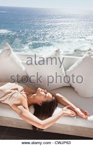 Serena donna posa sul divano con vista sull'oceano Foto Stock