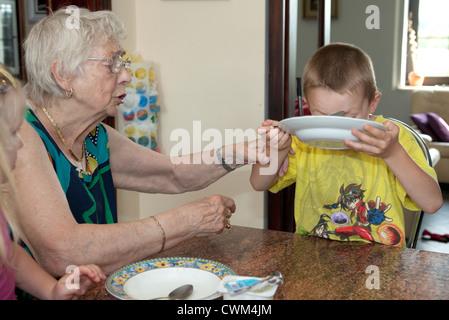 Il polacco grande nonna aiutando pronipote di finire la sua età zuppa 86 e 6. Zawady Polonia centrale Foto Stock