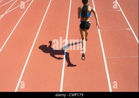Atleta femminile in esecuzione su via Foto Stock